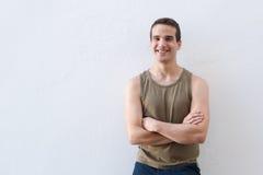 Uśmiechnięta facet pozycja przeciw białemu tłu z rękami krzyżować zdjęcia stock
