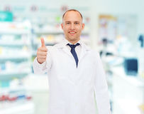 Uśmiechnięta farmaceuta pokazuje aprobaty przy apteką Fotografia Stock