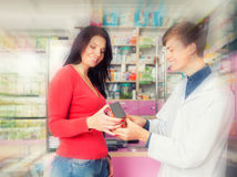 Uśmiechnięta farmaceuta pokazuje pudełko klient Zdjęcie Royalty Free