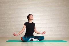 Uśmiechnięta i marzycielska kobieta robi joga ćwiczy obsiadanie w lotosie Zdjęcie Royalty Free