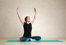 Uśmiechnięta i marzycielska kobieta robi joga ćwiczy obsiadanie w lotosie Zdjęcia Royalty Free