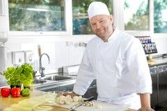 Uśmiechnięta i ufna szef kuchni pozycja w wielkiej kuchni Fotografia Stock