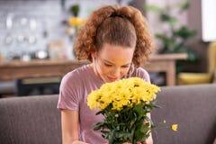 Uśmiechnięta imbirowa dziewczyna wącha silnego perfumowanie kwiaty obrazy stock
