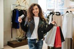 Uśmiechnięta kędzierzawa młoda dama trzyma kartę debetową z torba na zakupy Zdjęcie Royalty Free