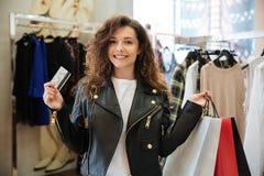 Uśmiechnięta kędzierzawa młoda dama trzyma kartę debetową z torba na zakupy Obrazy Stock