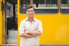 Uśmiechnięta kierowca autobusu pozycja z rękami krzyżować Obrazy Royalty Free