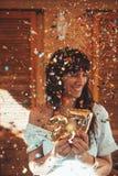 Uśmiechnięta kobieta świętuje jej 27th urodziny z złotymi liczbami i confetti obraz royalty free
