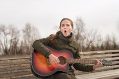 Uśmiechnięta kobieta bawić się gitarę Obraz Royalty Free