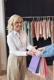 uśmiechnięta kobieta bierze torba na zakupy od sklepowego asystenta podczas gdy robiący zakupy Obraz Royalty Free