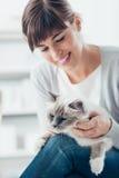 Uśmiechnięta kobieta cuddling jej kota Obrazy Royalty Free