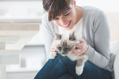 Uśmiechnięta kobieta cuddling jej kota Obrazy Stock
