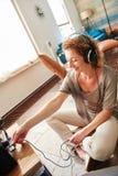 Uśmiechnięta kobieta czopuje w hełmofonach w system dźwiękowego Fotografia Stock