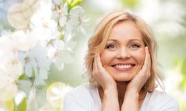 Uśmiechnięta kobieta dotyka jej twarz w białej koszulce obrazy royalty free