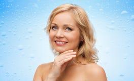 Uśmiechnięta kobieta dotyka twarz z nagimi ramionami Zdjęcie Royalty Free