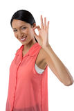 Uśmiechnięta kobieta gestykuluje zadowalającego ręka znaka przeciw białemu tłu Obrazy Royalty Free