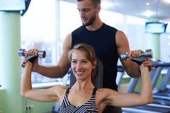 Uśmiechnięta kobieta i ogłoszenie towarzyskie trener ćwiczy w gym obrazy stock