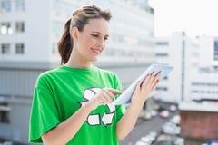 Uśmiechnięta kobieta jest ubranym przetwarzający tshirt używać pastylkę obraz royalty free
