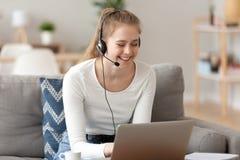 Uśmiechnięta kobieta jest ubranym słuchawki, używać laptop, patrzeje ekran obraz royalty free