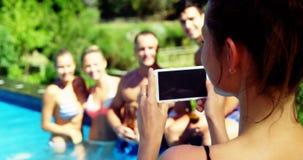 Uśmiechnięta kobieta klika fotografie przyjaciele od telefonu komórkowego blisko poolside zbiory