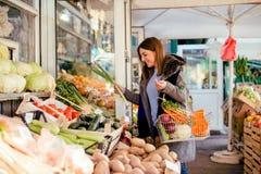Uśmiechnięta kobieta kupuje różnorodnych warzywa obrazy stock