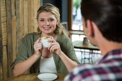 Uśmiechnięta kobieta ma kawę z mężczyzna w kawiarni Zdjęcia Stock
