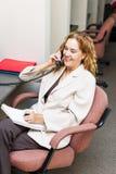 Uśmiechnięta kobieta na telefonie przy biurowym biurkiem obraz stock