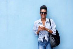 Uśmiechnięta kobieta opiera przeciw błękit ścianie z filiżanką i purs Obrazy Stock