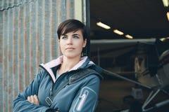 Uśmiechnięta kobieta opiera przeciw hangar ścianom Obrazy Stock