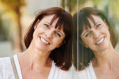 Uśmiechnięta kobieta opiera przeciw odbiciu w budynku obraz royalty free