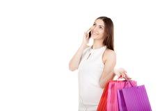 Uśmiechnięta kobieta opowiada na smartphone z kolorowymi torba na zakupy Obraz Royalty Free
