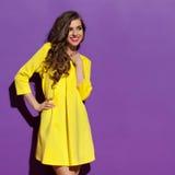 Uśmiechnięta kobieta Patrzeje Daleko od W Żółtej Mini sukni obraz royalty free