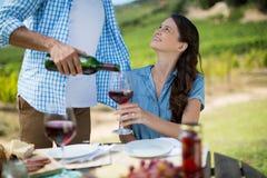 Uśmiechnięta kobieta patrzeje mężczyzna dolewania czerwone wino w szkle Obrazy Stock