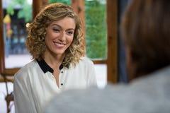 Uśmiechnięta kobieta patrzeje mężczyzna w sklep z kawą Obrazy Stock