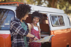 Uśmiechnięta kobieta patrzeje mężczyzna z mapą Obrazy Royalty Free