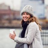 uśmiechnięta kobieta pije kawę od papierowej filiżanki pozyci na rzecznym bulwarze i cieszy się widok obraz royalty free