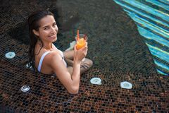 Uśmiechnięta kobieta pije koktajl w wodzie zdjęcia stock