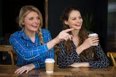 Uśmiechnięta kobieta pokazuje coś przyjaciel w sklep z kawą fotografia royalty free