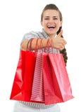 Uśmiechnięta kobieta pokazywać aprobaty z torba na zakupy fotografia stock