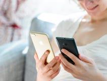 Uśmiechnięta kobieta porównuje iphone 7 plus vs Microsoft telefon obraz stock