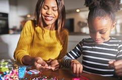 Uśmiechnięta kobieta pracuje z dzieckiem na paciorkowatym projekcie Zdjęcia Royalty Free