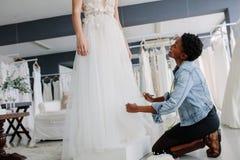 Uśmiechnięta kobieta robi dostosowaniu bridal toga obrazy royalty free