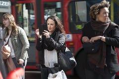 Uśmiechnięta kobieta robi fotografii na telefonie na tle przelotny autobus Zdjęcia Stock