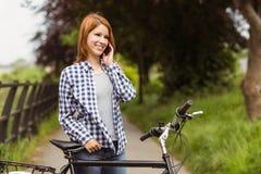 Uśmiechnięta kobieta robi rozmowie telefonicza przed jej rowerem Fotografia Stock