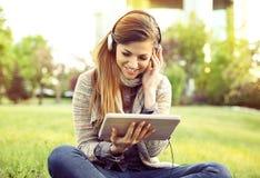 Uśmiechnięta kobieta słucha muzyka z pastylką i hełmofonami siedzi outdoors w miasto parku obraz royalty free