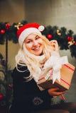 Uśmiechnięta kobieta Siedzi Blisko choinki W Zdjęcie Stock
