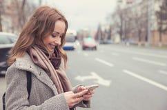 Uśmiechnięta kobieta sprawdza emaila przez telefonu komórkowego czekać na autobus obrazy royalty free