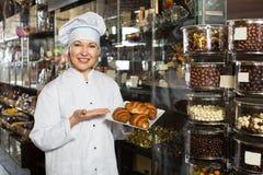 Uśmiechnięta kobieta sprzedaje wyśmienicie deser zdjęcia royalty free