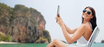 Uśmiechnięta kobieta sunbathing na plaży z pastylka komputerem osobistym Obraz Stock