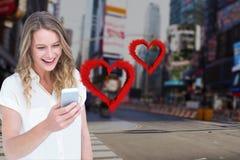 Uśmiechnięta kobieta texting na telefonie komórkowym z cyfrowo wytwarzającymi czerwonymi sercami Zdjęcie Stock