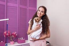 Uśmiechnięta kobieta trzyma ślicznego mokrego Yorkshire teriera psa zawijający w ręczniku po skąpania obrazy royalty free